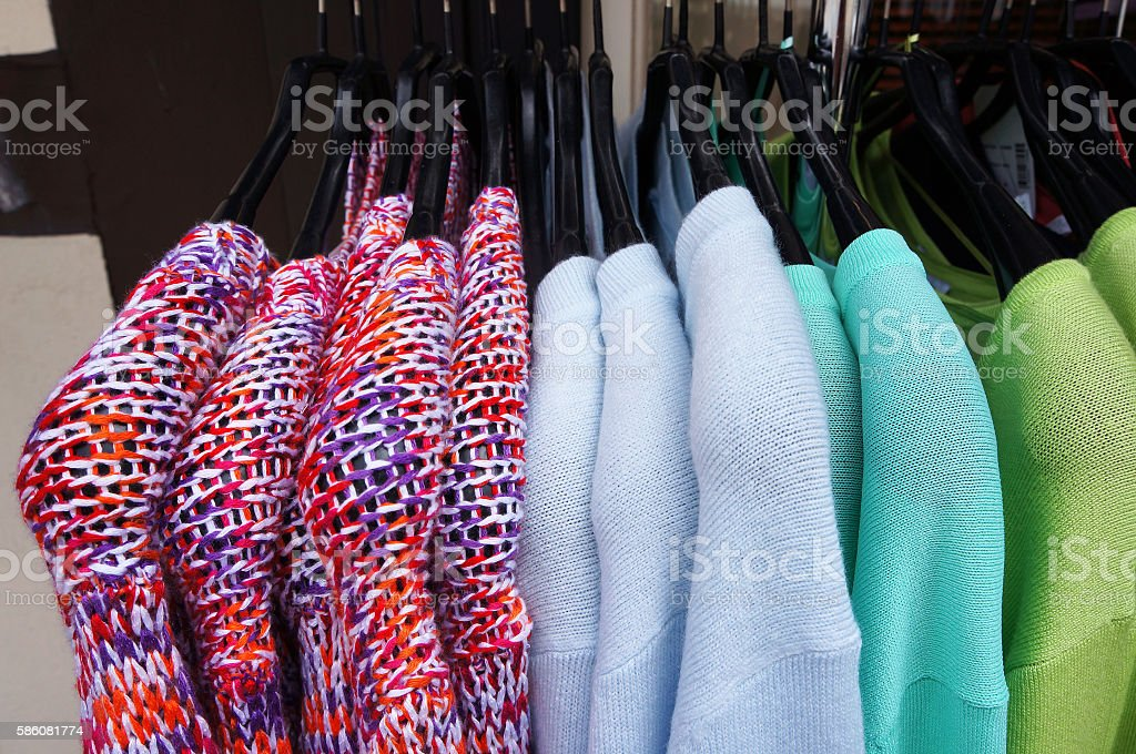 Pullovers on hangers. stock photo