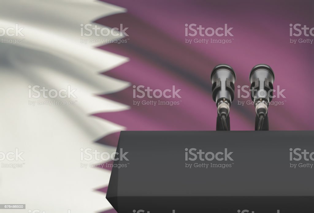 Pulpit and two microphones with a national flag on background - Qatar stock photo