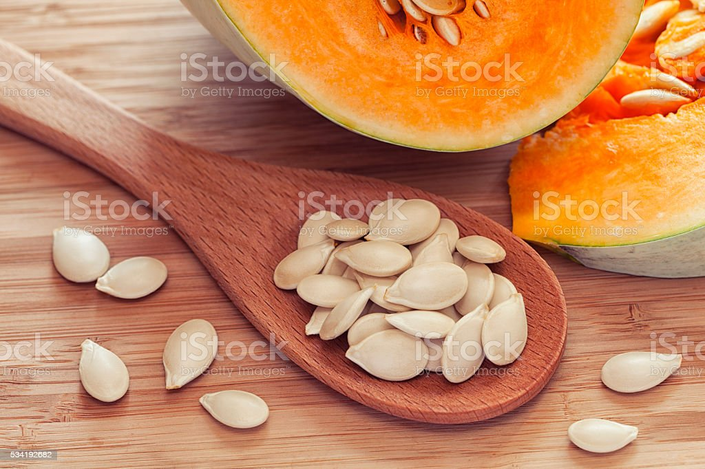 Pumkin seeds inside of wooden spoon stock photo