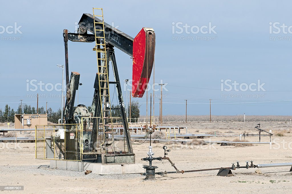 Pump jack and pipelines in oil field of central California stock photo