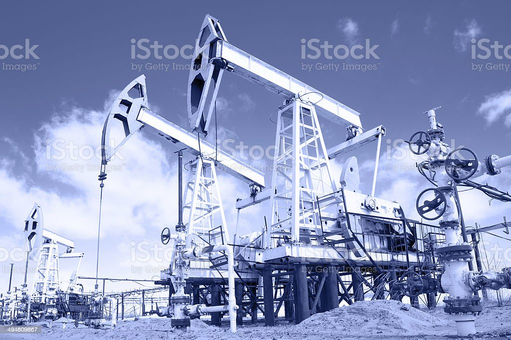 Pump jack and wellhead. Toned. stock photo