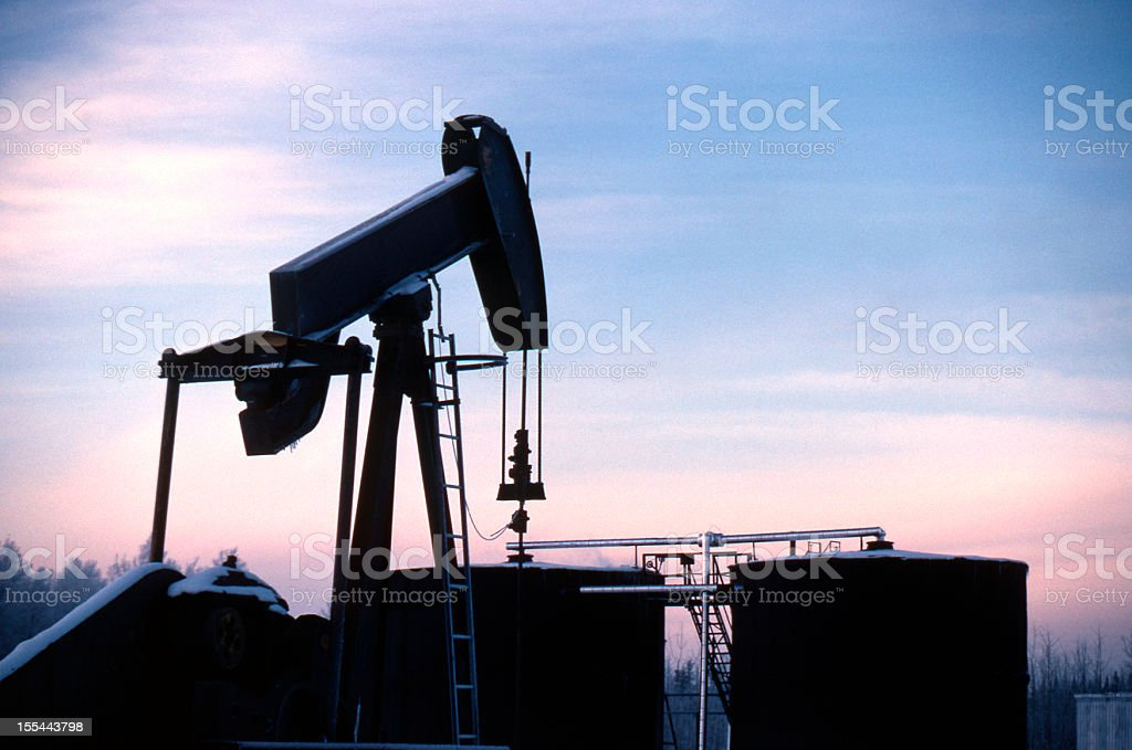 Pump Jack at Dusk, covered in Snow stock photo