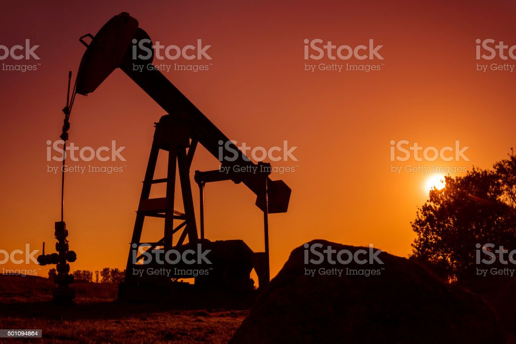 Pump Jack on field at sunset stock photo