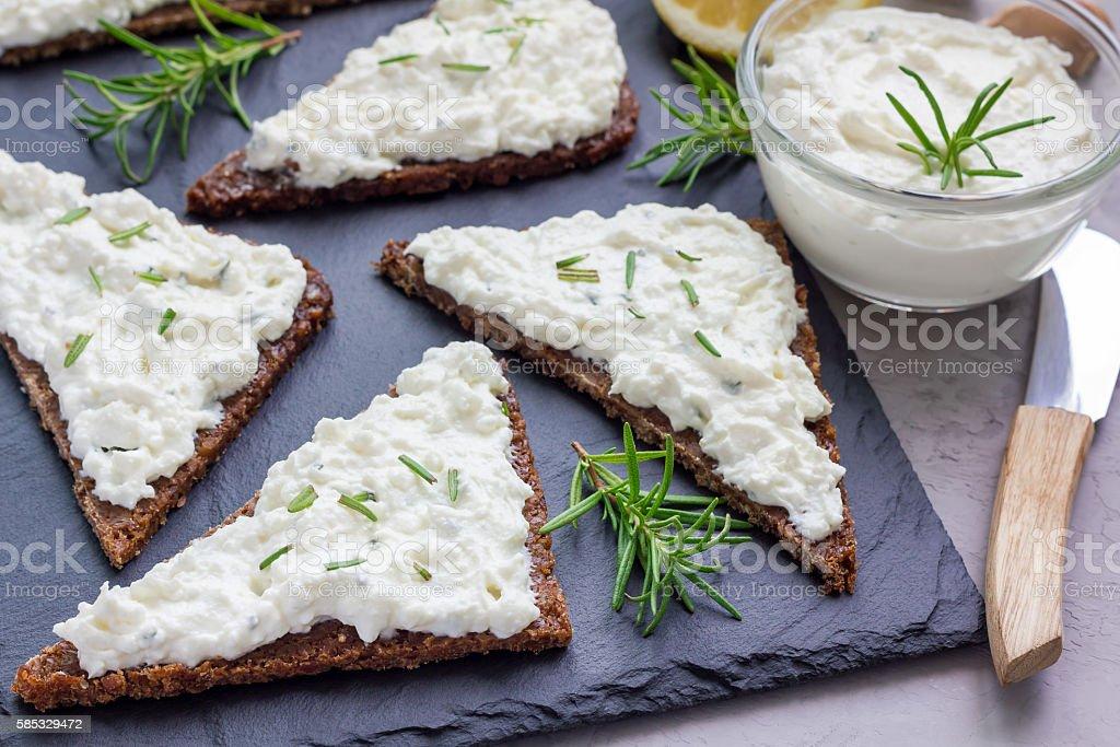 Pumpernickel bread with feta, cream cheese, rosemary, lemon, garlic dip stock photo