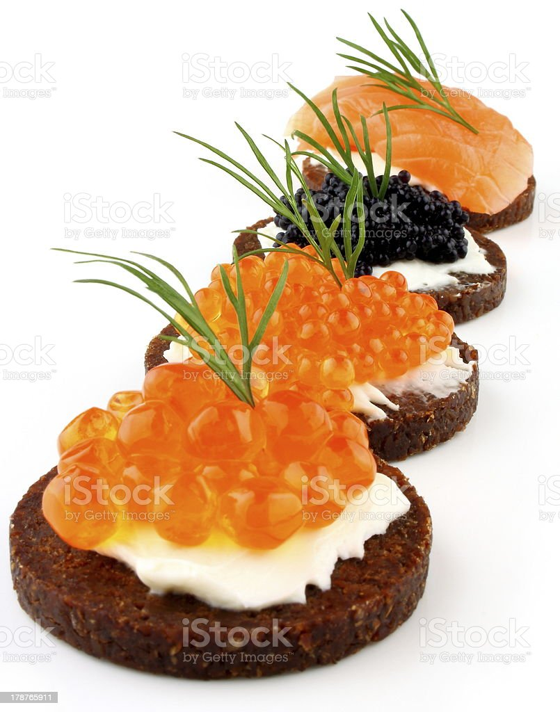Pumpernickel bread with salmon, trout and sturgeon caviar royalty-free stock photo