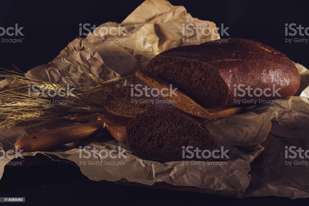 Pumpernickel Bread With Wheat On Wrinkled Brown Paper. stock photo