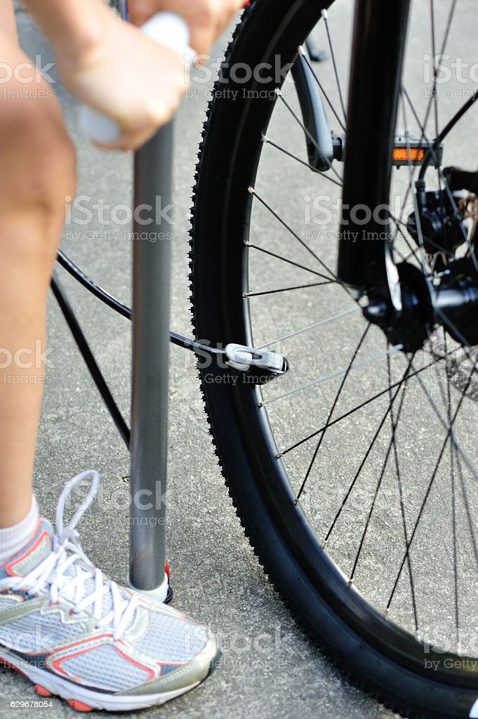 pumping air into the wheel of bycle. stock photo
