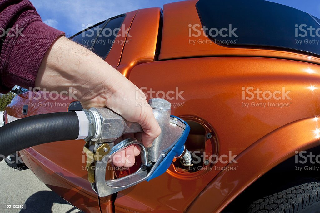 Pumping Gas Into Vehicle on a Sunny Day royalty-free stock photo