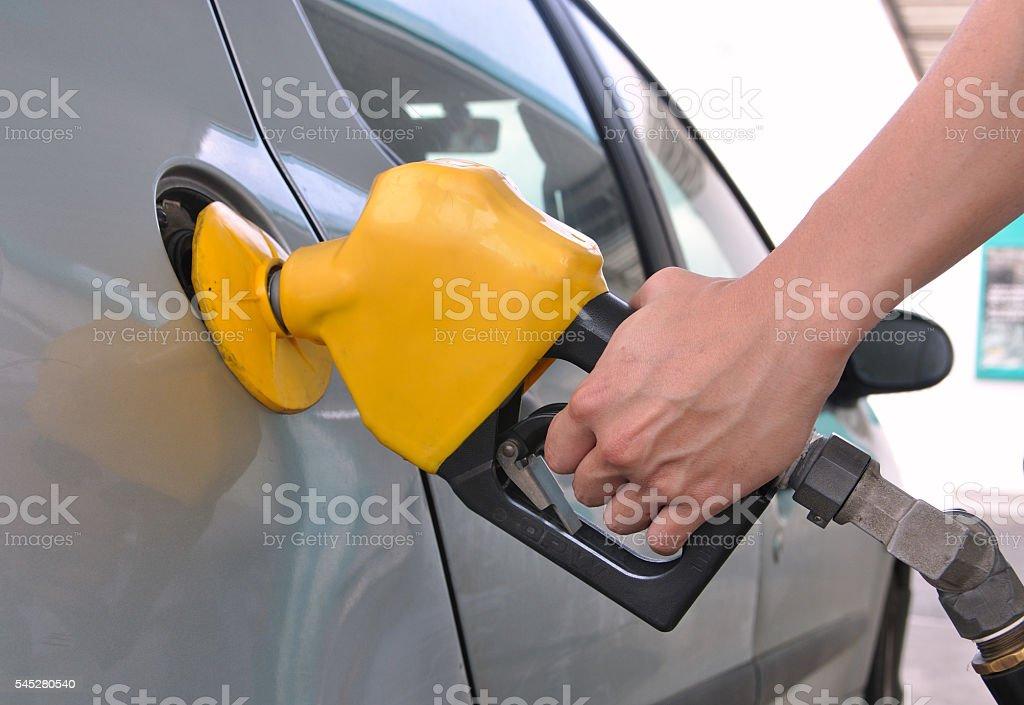 Pumping gasoline from a fuel pump using a yellow nozzle foto de stock libre de derechos