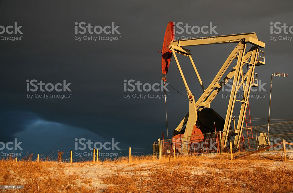 Pumpjack and Stormy Sky on Oil Field stock photo