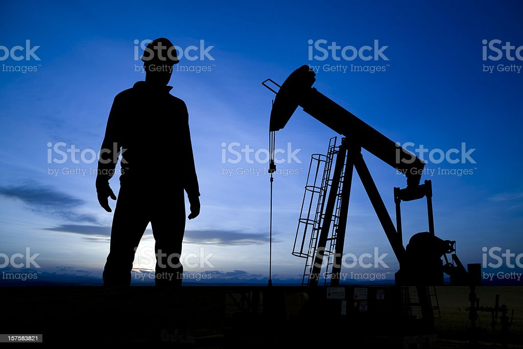 Pumpjack and Worker at dusk royalty-free stock photo