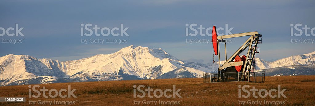 Pumpjack Panorama with Canadian Rockies in Distance stock photo
