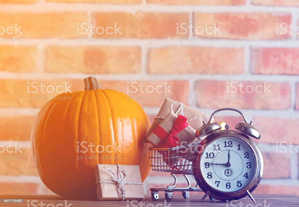 pumpkin and alarm clock with shopping cart full of gifts stock photo