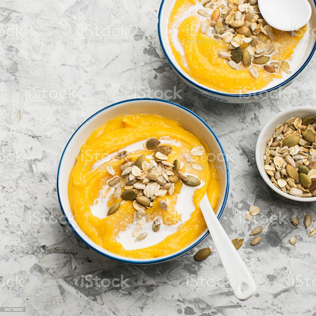 Pumpkin and apple cider soup with a topping of crispy toasted pumpkin seeds, sunflower seeds and oat flakes in a serving bowl on a light background. Top View. stock photo