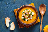 Pumpkin and carrot soup with cream, croutons on creative blue