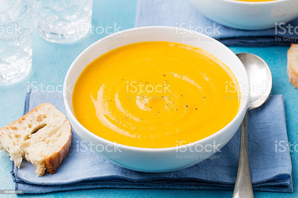 Pumpkin and carrot soup with cream on blue stone background. stock photo