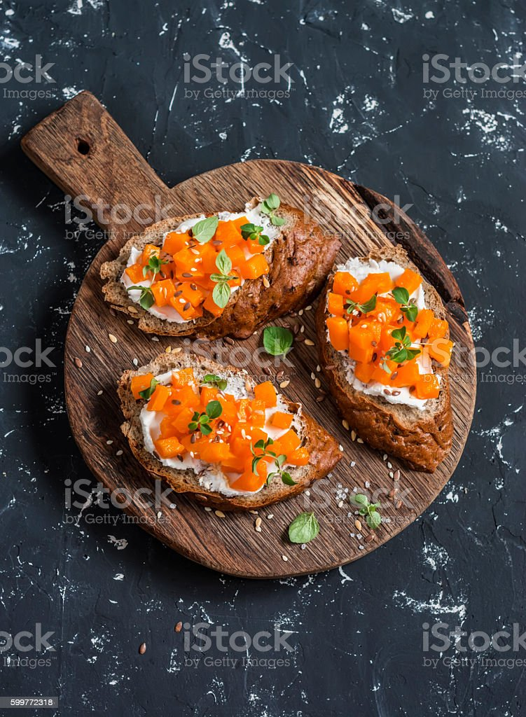 Pumpkin and goat's cheese bruschetta on a wooden cutting board stock photo