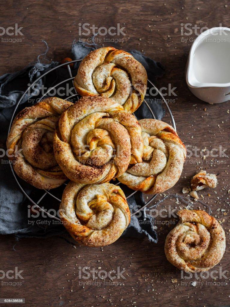 Pumpkin cinnamon puff pastry swirls rolls on a wooden table stock photo