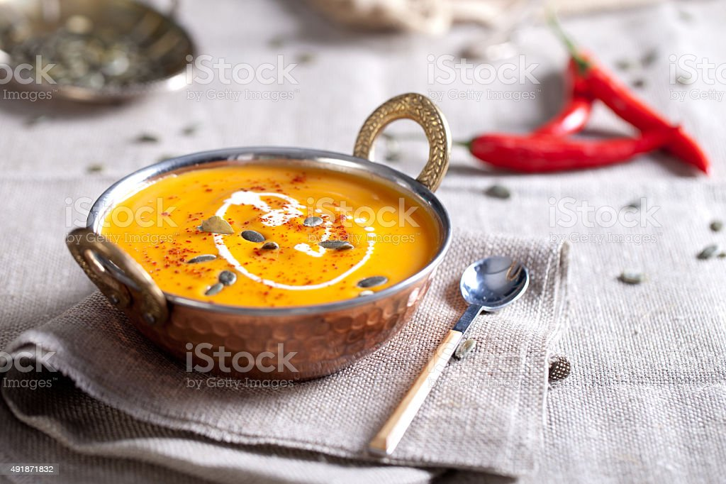 Pumpkin cream soup with chili and seeds stock photo