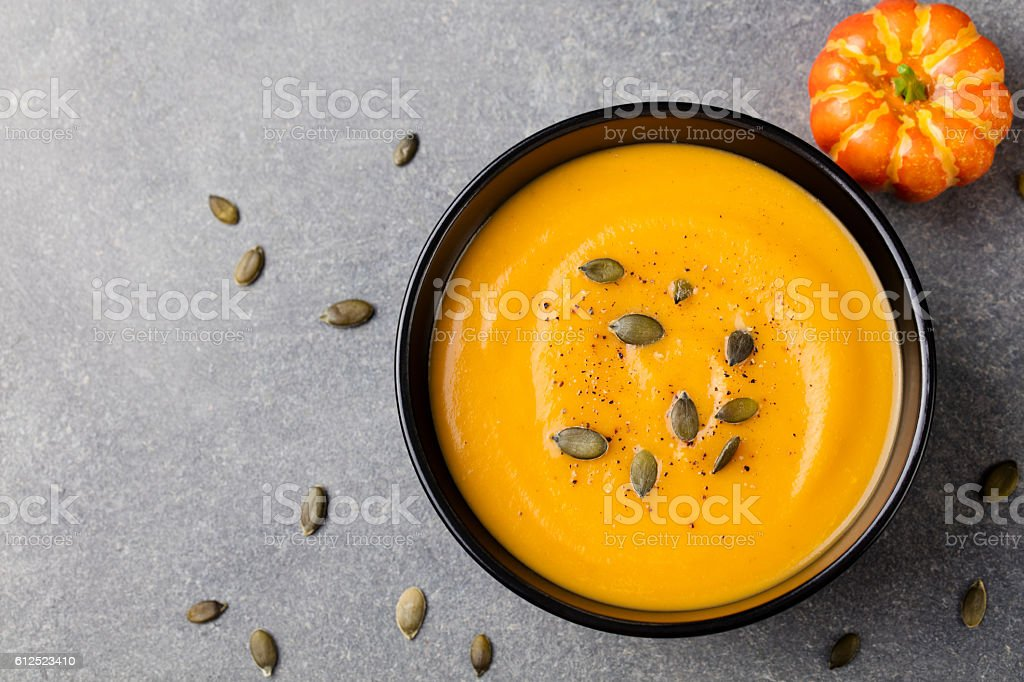 Pumpkin cream soup with seeds in a black bowl. stock photo