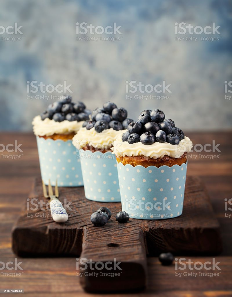 Pumpkin cupcakes decorated with cream cheese frosting and fresh blueberries stock photo