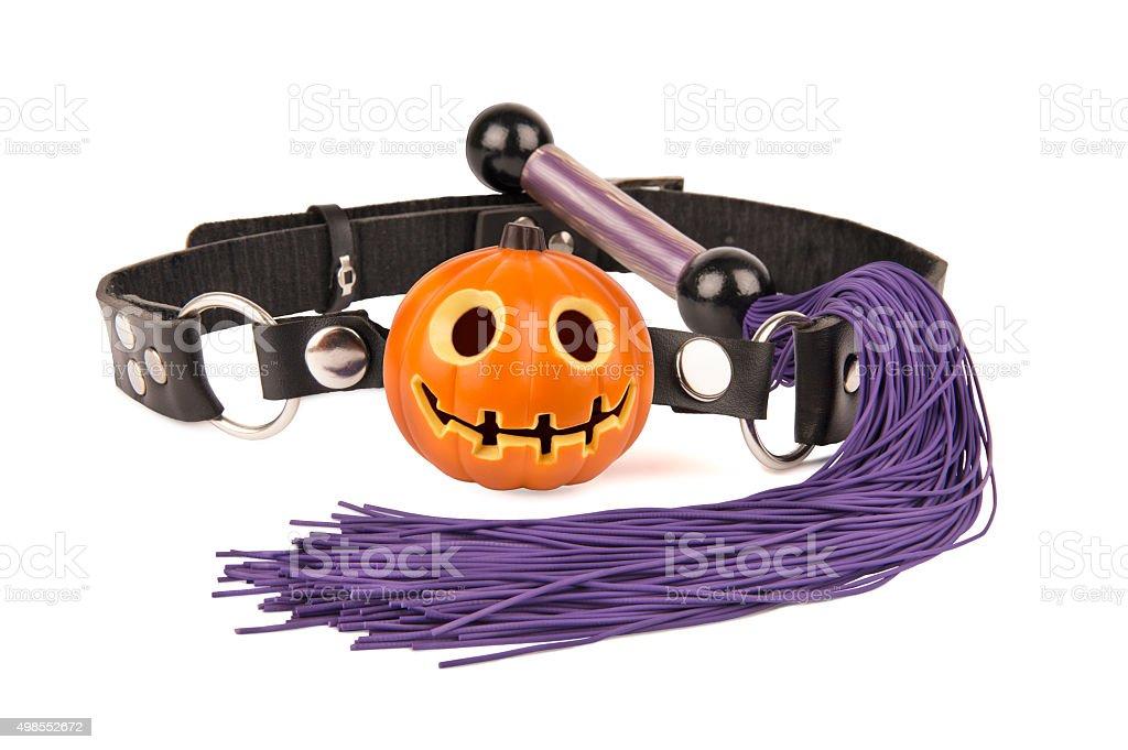 Pumpkin head ball gag and whip stock photo