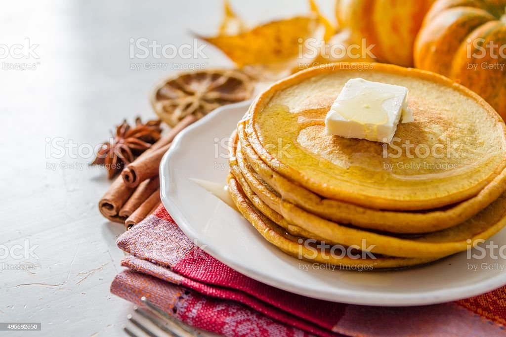 Pumpkin pancakes on white plate with butter and honey stock photo