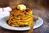 Pumpkin pancakes with chocolate drops on a rustic background.