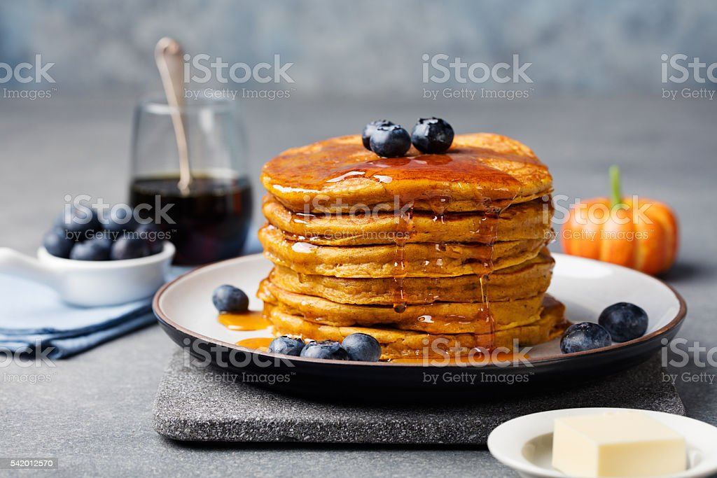 Pumpkin pancakes with maple syrup and blueberries on a plate. stock photo