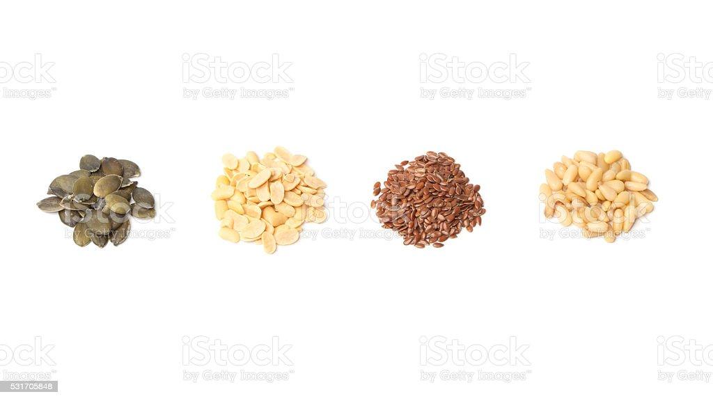 Pumpkin, peanut, linseed, pine seeds on white stock photo