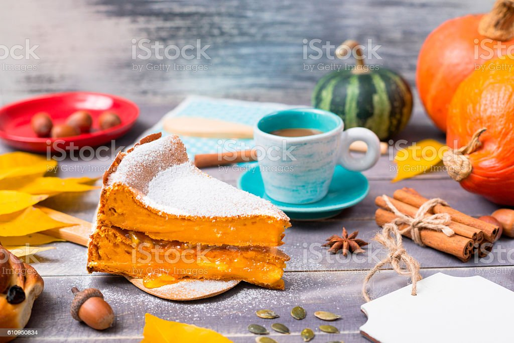 Pumpkin pie dusted with icing sugar with a cup of coffee stock photo