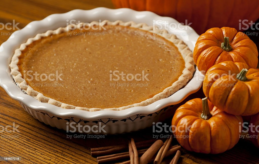 Pumpkin pie in white dish beside three pumpkins stock photo
