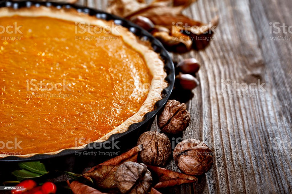 Pumpkin pie on a rustic table stock photo