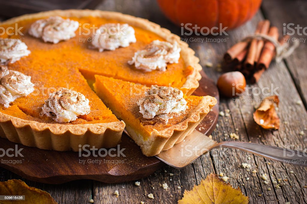pumpkin pie with whipped cream and cinnamon stock photo