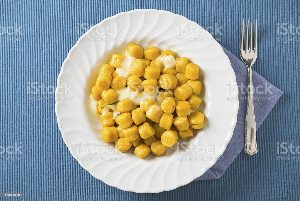 Pumpkin Potato Gnocchi with cheese and basil on blue background royalty-free stock photo