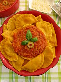 Pumpkin ravioli with tomato and olive sauce in red bowl