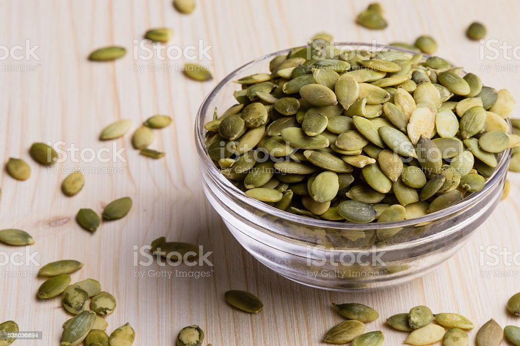 pumpkin seeds in a glass bowl stock photo