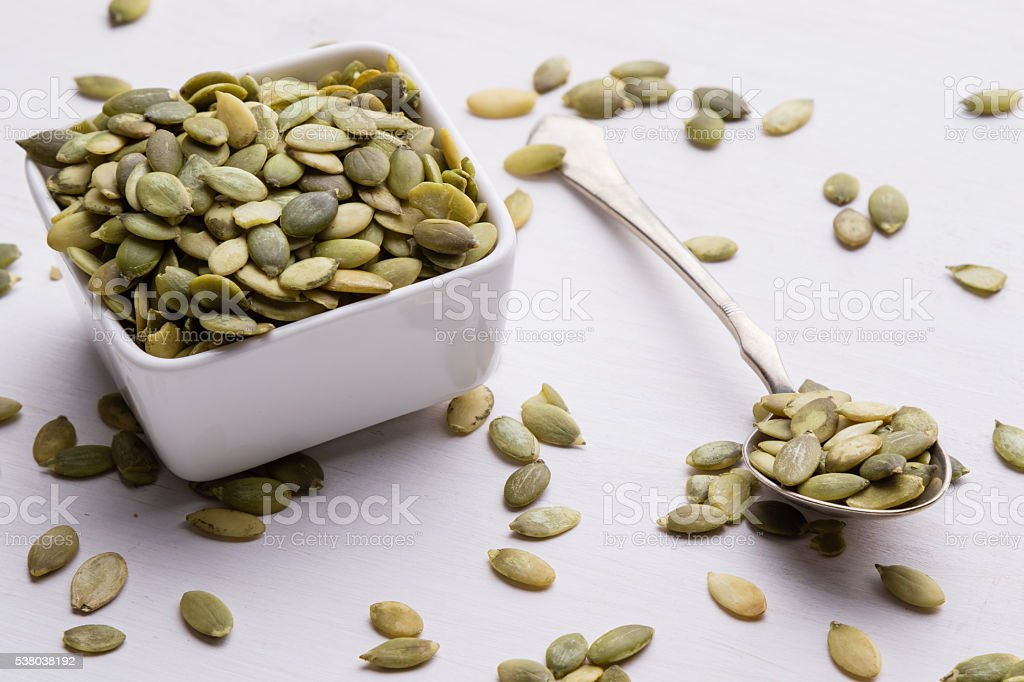 pumpkin seeds on white table with spoon and bowl stock photo