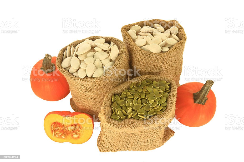 Pumpkin seeds with and without shell in burlap bags, pumpkins stock photo