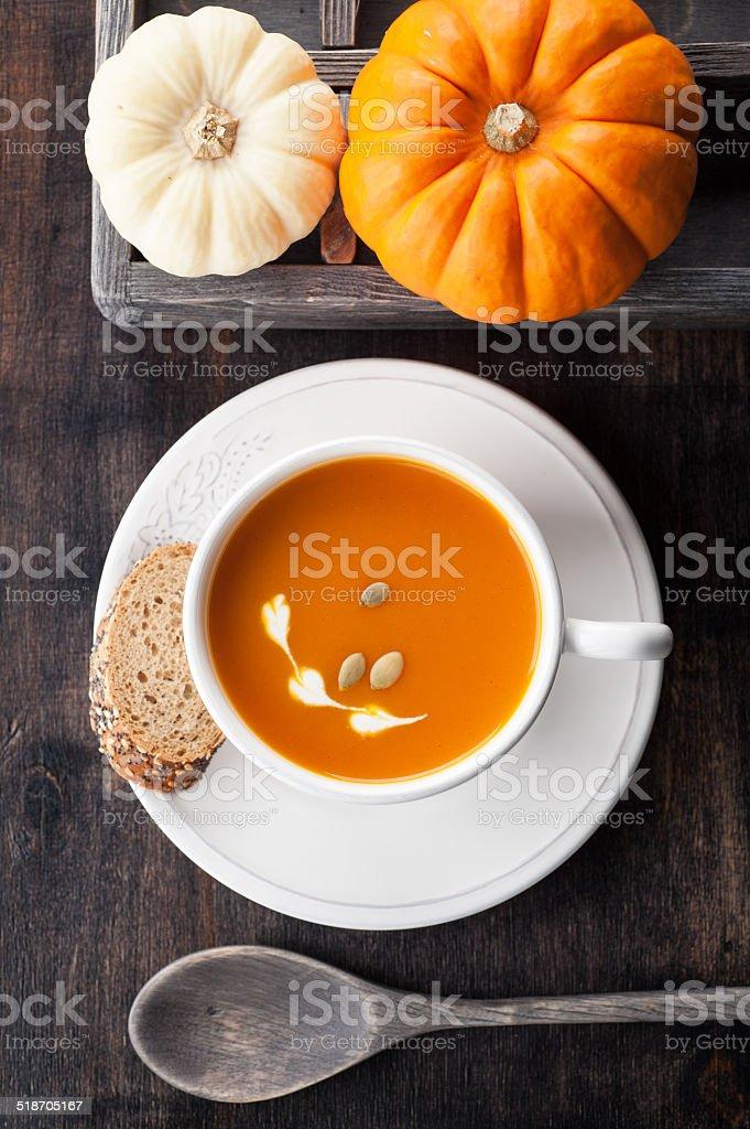 Pumpkin soup and raw pumpkins stock photo