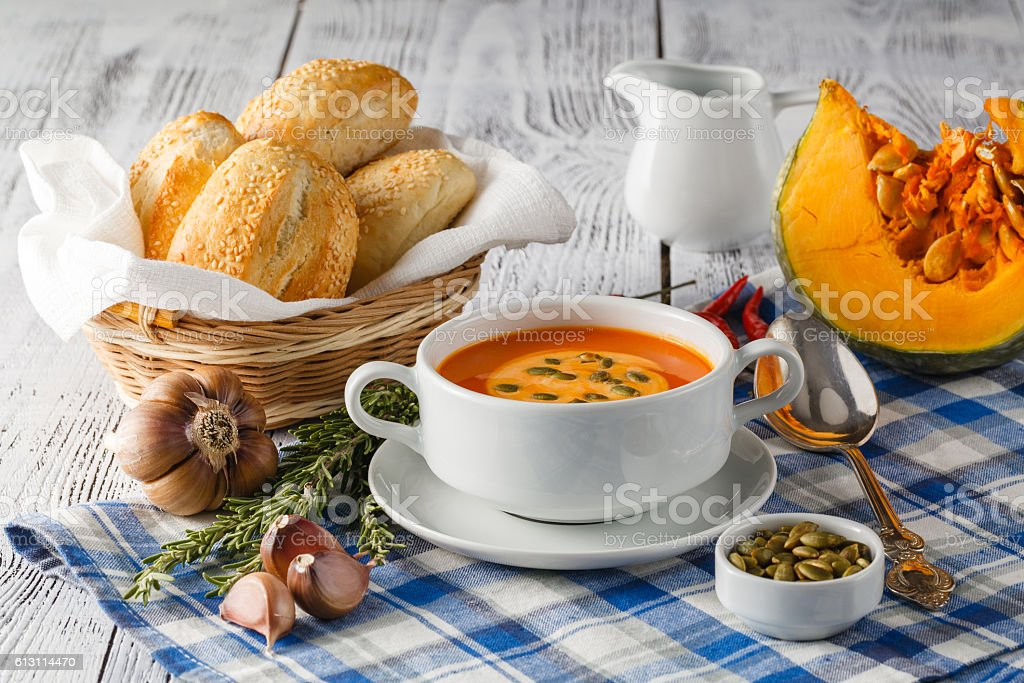 Pumpkin soup in a bowl with fresh pumpkins stock photo