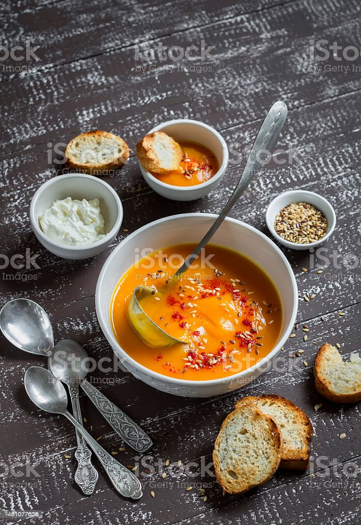 pumpkin soup in a white bowl on a dark  background stock photo