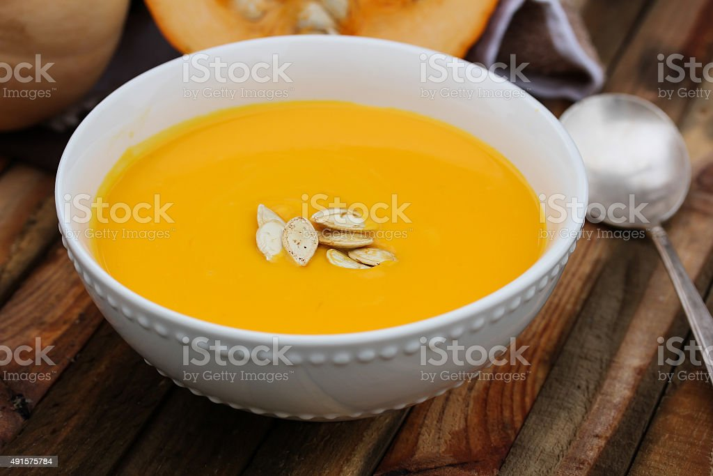 Pumpkin soup in a white bowl with wooden backgrund stock photo