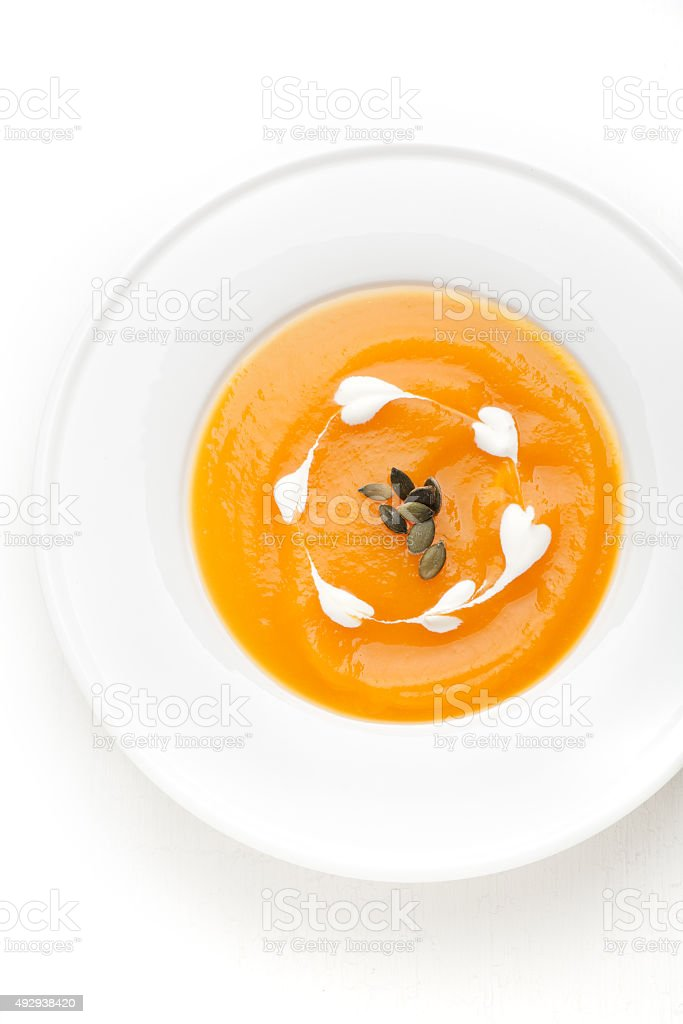 Pumpkin soup in a white plate. Top view, vertical stock photo