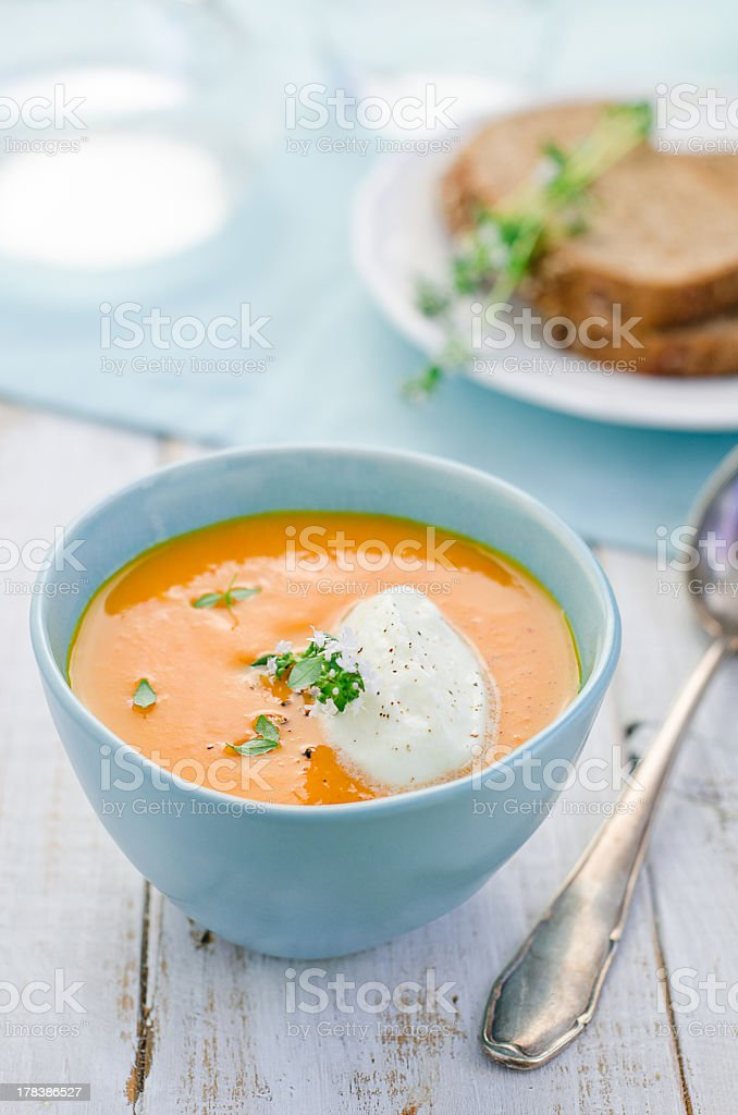 Pumpkin soup in blue bowl with spoon and sandwich in back stock photo