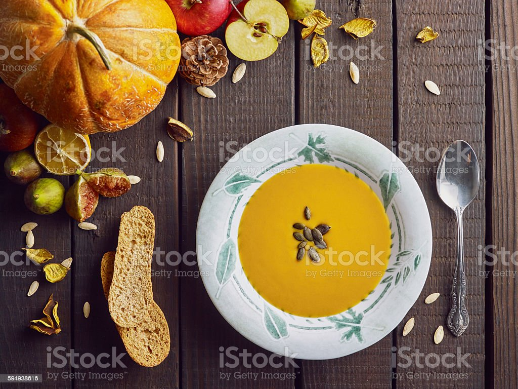 Pumpkin soup in the plate on a wooden table. stock photo