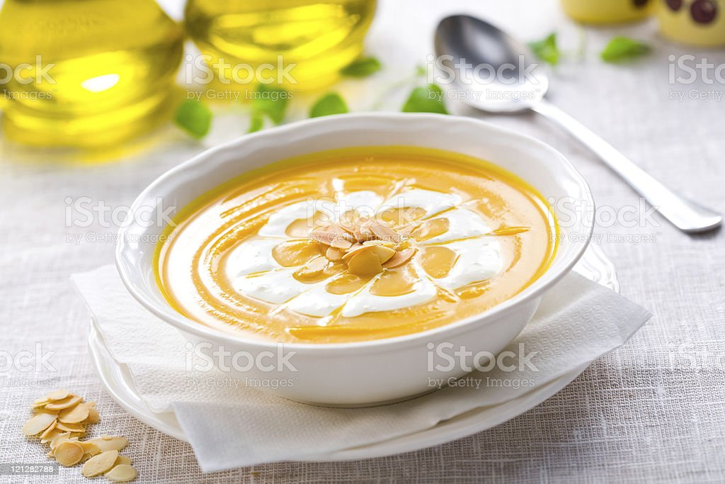 Pumpkin soup in white dish with seeds and cream on top stock photo