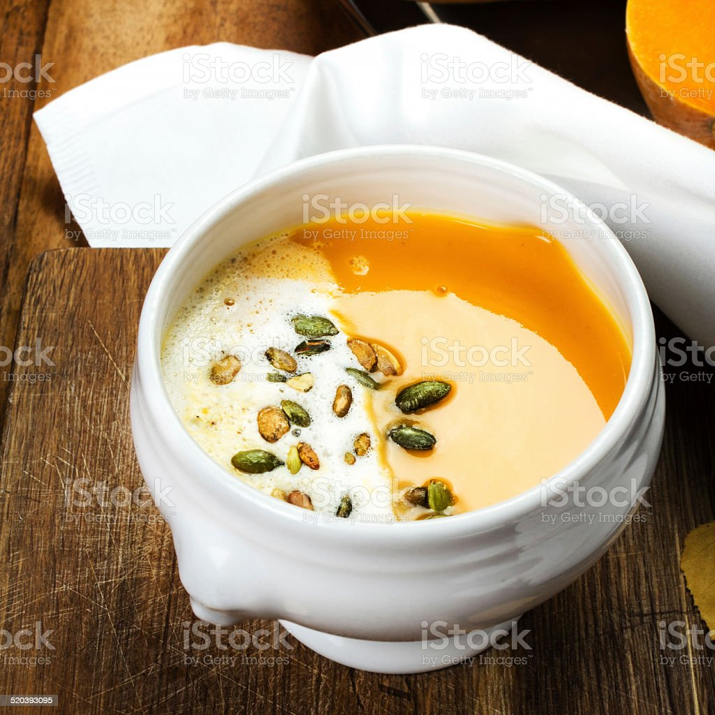 Pumpkin soup in white plate on wooden table stock photo