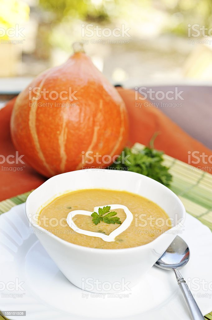 Pumpkin soup with cream heart and parsley garnish royalty-free stock photo