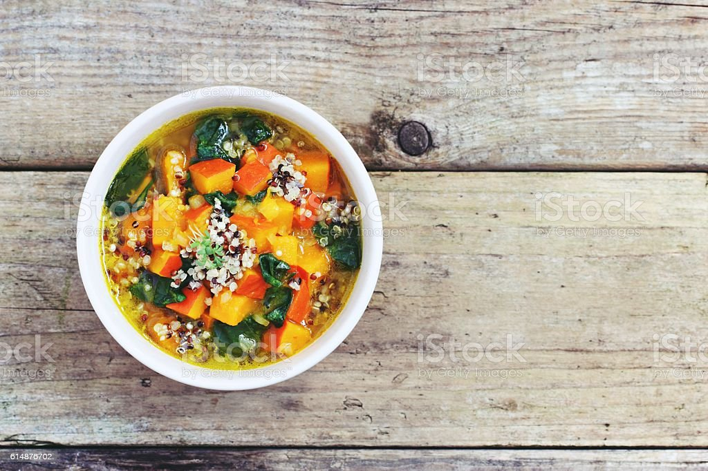 Pumpkin soup with quinoa and spinach. stock photo